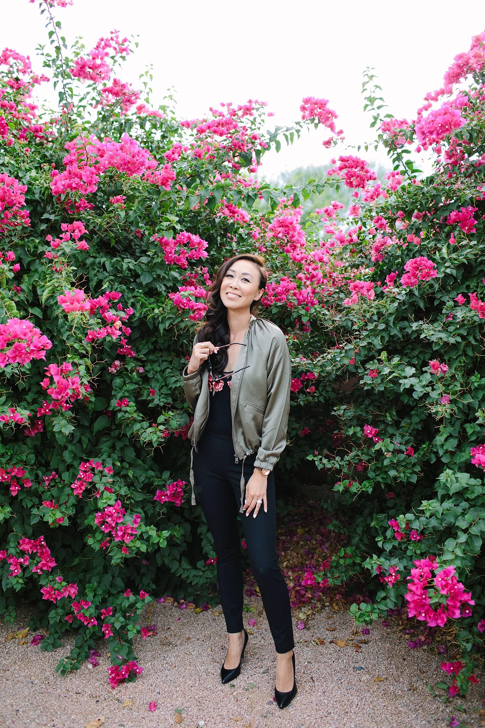 diana elizabeth lifestyle blogger in black devon-fit bi-stretch leggings and satin bomber jacket by banana republic standing in front of pink bougevvilla plants black netting bodysuit