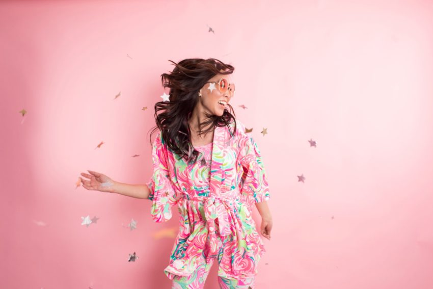 Lilly Pulitzer Christmas pajama party Diana Elizabeth in front of pink background and star confetti