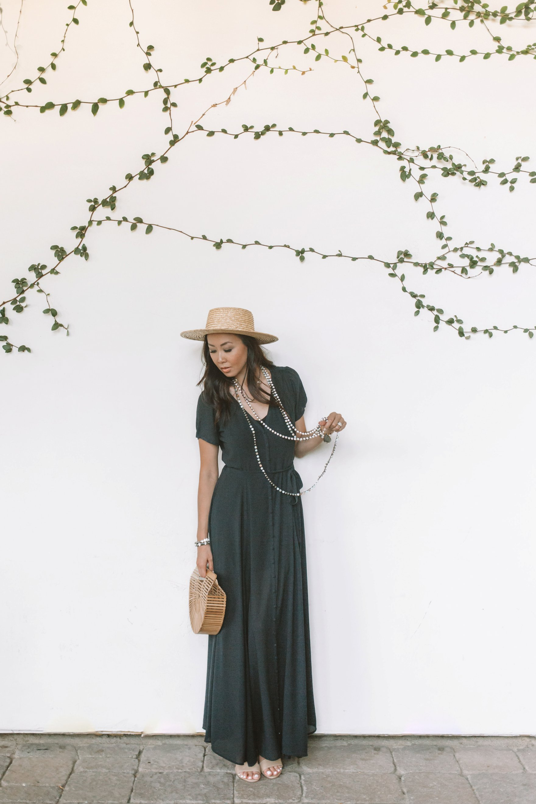 black maxi dress long pearl crochet necklace with hat, sunny day in scottsdale blogger Diana Elizabeth in front of white vines