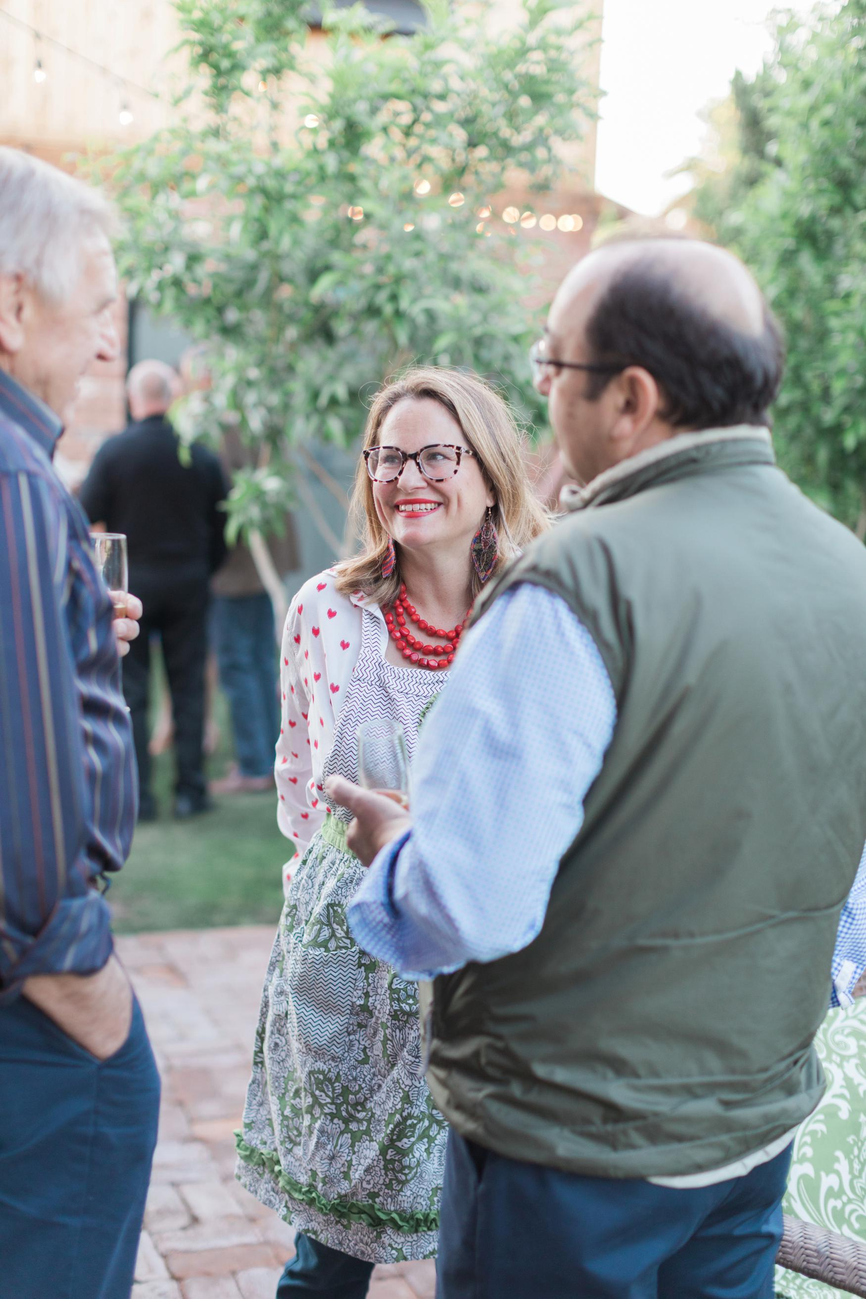 Boho Farm and Home Dinner theme Spain in backyard tapas. guests and host Caroline Van Skyle mingling before dinner is served.