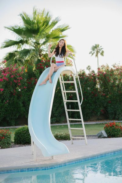 yandy affordable stylish swimsuits - on lifestyle blogger Diana Elizabeth - white sailor one piece swimsuit, posing on pool slide