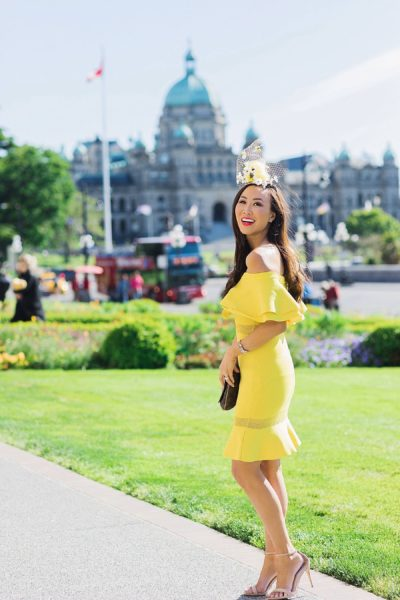 yellow fascinator hat bee hive high tea for bridal shower wedding celebration at empress hotel Victoria Canada wearing yellow off shoulder ruffle dress on blogger Diana Elizabeth standing in front of the Parliament building