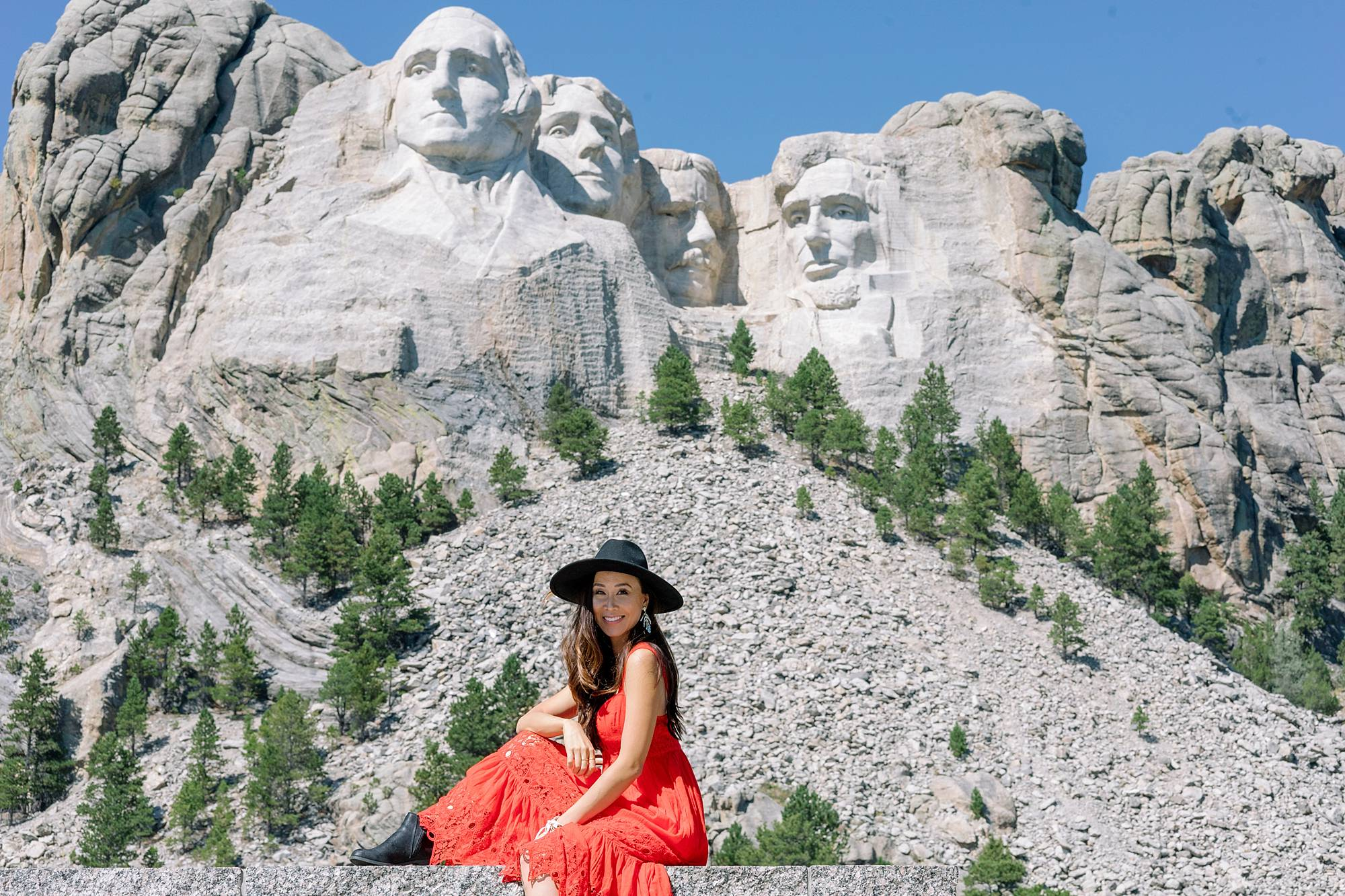 Mount Rushmore in south Dakota posing is Diana Elizabeth lifestyle blogger wearing free people red maxi dress and black wool hat