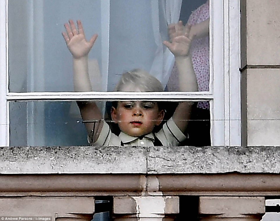 The three-year-old was snapped peering out of the window behind the balcony taking in the thousands of people below