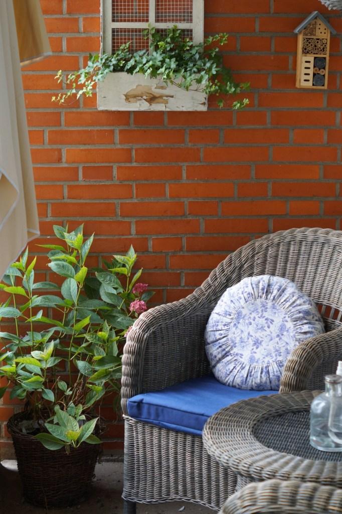 Korbmöbel stehen auf dem Balkon