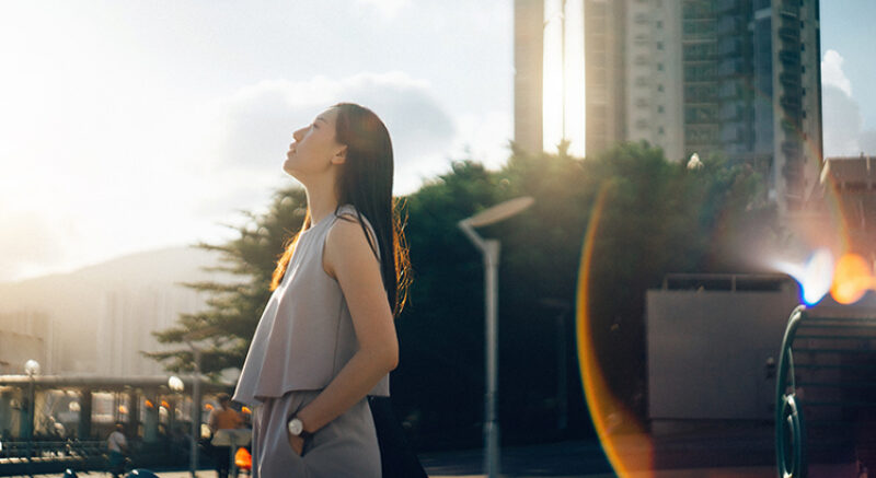 Young Asian woman looking up to sky in deep thought in the city at sunset