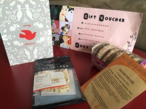 Diane's gifts: a comic voucher, a card, a nanoblock dinosaur, German style gingerbread and heartsease seeds.