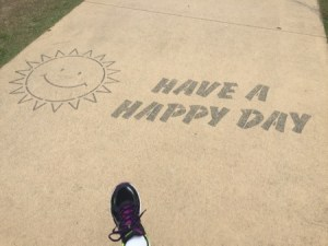 "Diane's foot on the path in the park. There's a sun symbol painted on the path, to the right of it the words ""Have a happy day""."