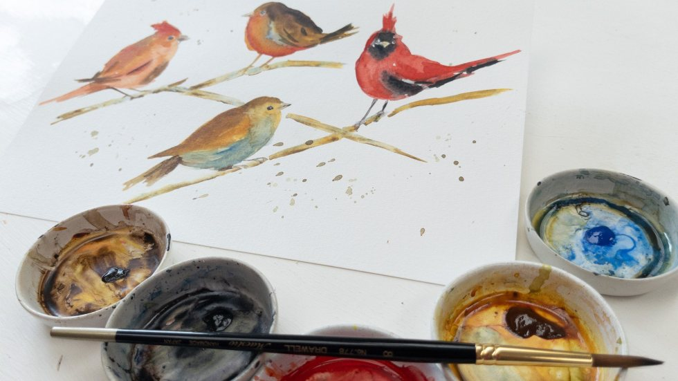 watercolor painting of robins and red cardinals with paints in ceramic dishes and Drawell round brush