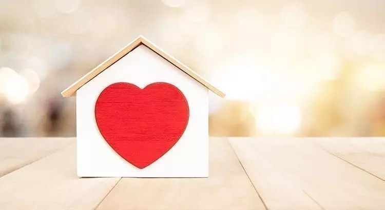 small wooden house with a heart in it, sitting on a table