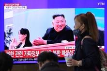 Una mujer pasa en frente de una pantalla de televisión en la estación de trenes de Seúl, donde se ve la imagen del líder norcoreano Kim Jong Un y su hermana Kim Yo Jong, el sábado 2 de mayo de 2020.