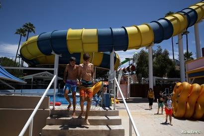 Huéspedes salen de la piscina en un tobogán de agua en el parque acuático Golfland Sunsplash después de que se aliviaron las restricciones de la enfermedad por coronavirus (COVID-19) en Mesa, Arizona, EE. UU., 15 de mayo de 2020.