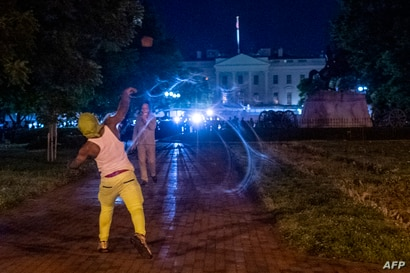 TOPSHOT - Protesters face off with police outside the White House in Washington, DC, early on May 30, 2020, during a…