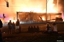 Protesters gather near the Minneapolis Police third precinct to watch a construction site burn after a white police officer was…