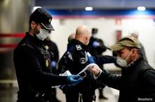 Un policía español reparte tapabocas en una estación del metro de Madrid. El lunes, el gobierno permitió que los trabajarores de construcción y fábricas, regresaran a sus empleos.