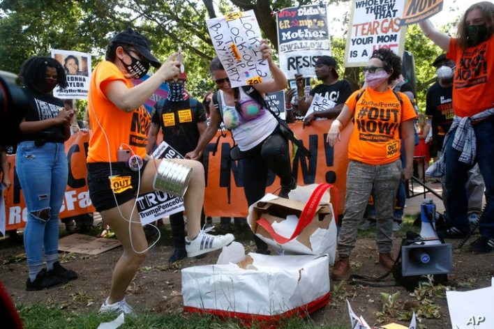 Protesters destroy a mock birthday cake for President Donald Trump on Trump's birthday, Sunday, June 14, 2020, in Lafayette…