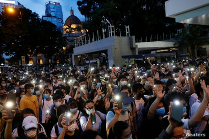 Pro-democracy demonstrators march holding their phones with flashlights on during a protest to mark the first anniversary of a…