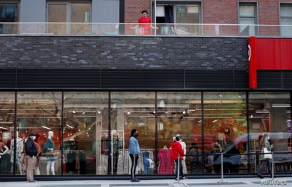 FILE PHOTO: FILE PHOTO: A man jumps rope on his apartment balcony above a Target store as shoppers wait at a social distance…