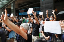 Supporters raise white paper to avoid slogans banned under the national security law as they support arrested anti-law protester outside Eastern court in Hong Kong