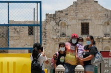 Visitors wearing masks to protect against the spread of COVID-19 pose for photos at the Alamo, which remains closed, in San…