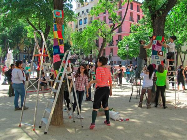 Tejido callejero en acción personas colgando los tejidos en los árboles