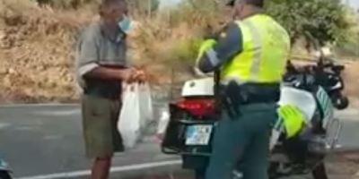 Un guardia civil de tráfico da su compra de comida a un indigente