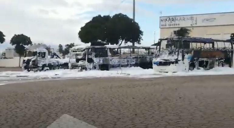 Arden dos autobuses y un camión en el aparcamiento de una gasolinera