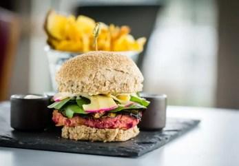 O hambúrguer vegetariano é feito com grão de bico, beterraba e erva finas, servido com legumes grelhados e queijo em pão integral ou clássico polvilhado com gergelim (Foto: divulgação)