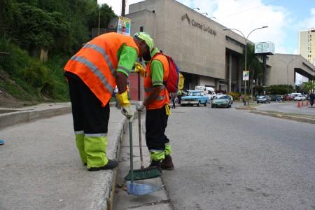 Cuadrillas de la alcaldía limpian la zona de acceso a la urbanización.
