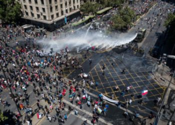 Aerial view showing riot police spraying water at demonstrators in Santiago, on the sixth straight day of street violence which erupted over a now suspended hike in metro ticket prices, on October 23, 2019. - A four-year-old child was killed during the latest round of protests against economic inequality in Chile, raising the death toll from five days of social unrest to 18 as unions launched a general strike on Wednesday. (Photo by Javier TORRES / AFP)