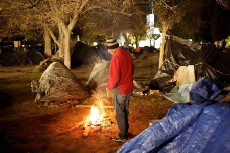 Foto de archivo de un hombre acampando en Ciudad Juárez mientras espera para solicitar una visa en EEUU calentándose junto a una fogata. Dic 17, 2019.  REUTERS/Jose Luis Gonzalez