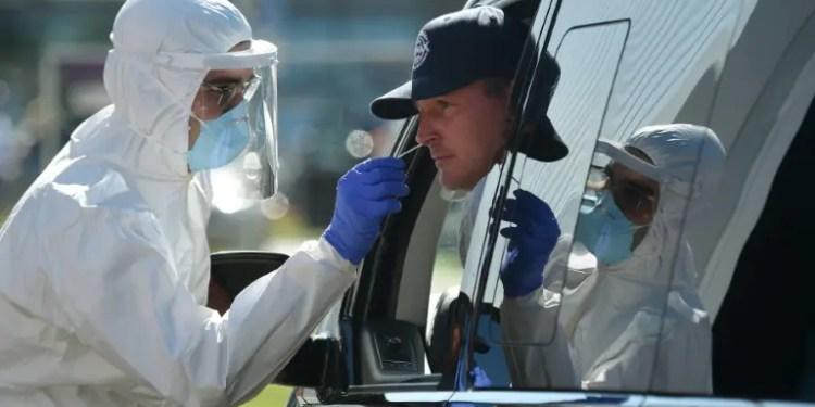 Un trabajador sanitario con indumentaria protectora toma una muestra de mucosa a un hombre en su automóvil para realizar una prueba de detección del coronavirus, este jueves 30 de julio de 2020 en un área de servicio en Alemania