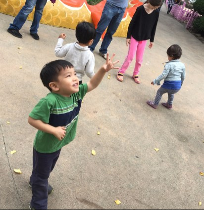 playing bubbles at fairyland (image of collin reaching up for bubbles with others children in the background)