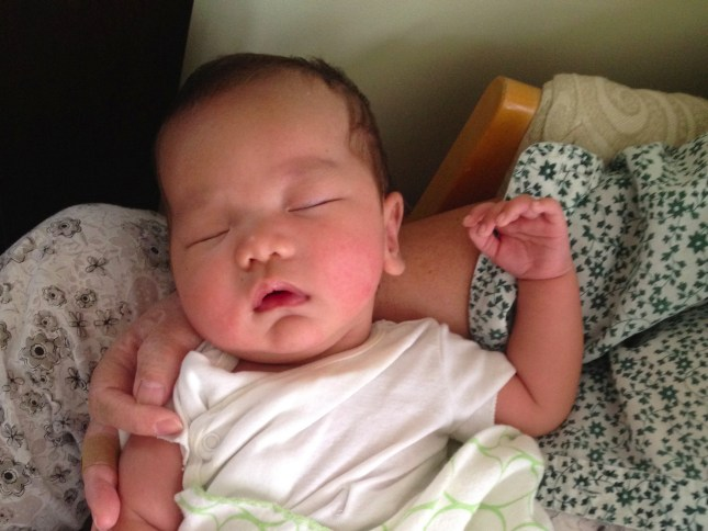 Image of Collin at 3 months peacefully asleep on grandma's lap with his tiny finger nails ready to be cut.