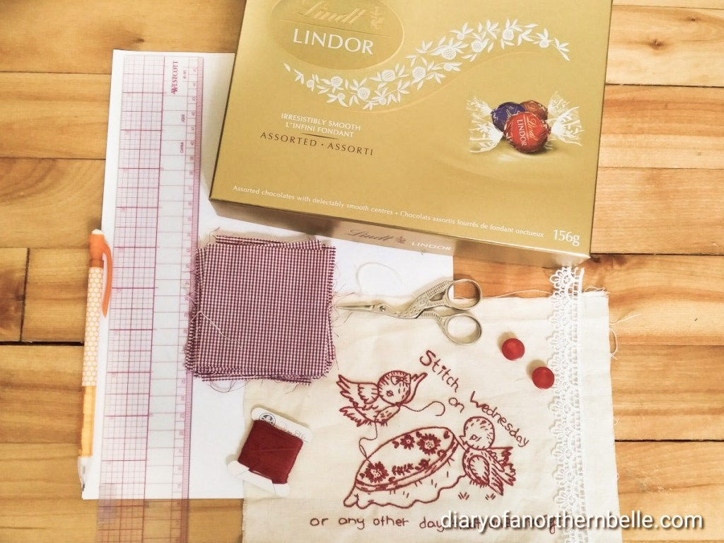 materials used to upcycle an old chocolate box: fabric, ruler, pencil, scissors, embroidered fabric to cover the lid