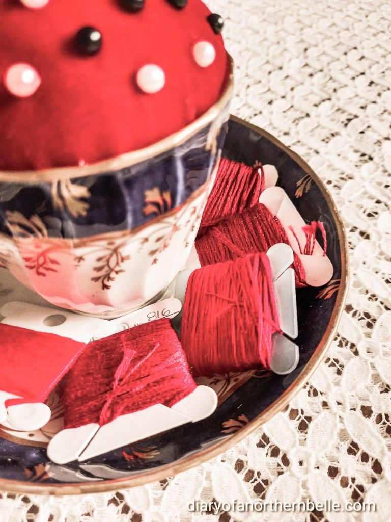 vintage teacup pincushion with close-up view of an assortment of red embroidery threads