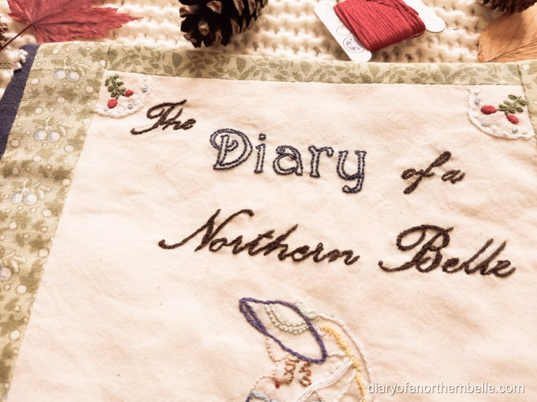 """close up view of the front cover embroidery; title """"The Diary of a Northern Belle"""" stitched to represent cursive letters; the head of the Southern Belle lady, and the little berries decorating the two upper corners"""