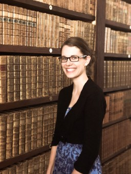 photo of Anne (author of the blog) standing in front of bookshelves filled with antique books