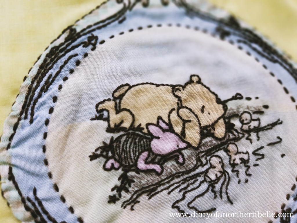 embroidered winnie-the-pooh fabric close-up, sewn onto yellow fabric