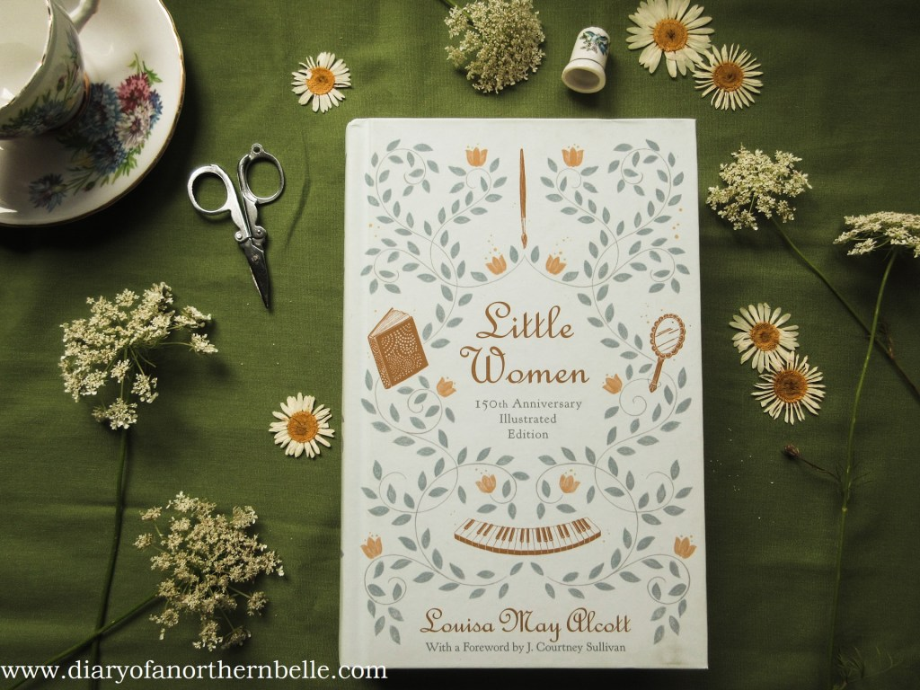 hardcover copy of little women by alcott surrounded by queen anne's lace and pressed daisies