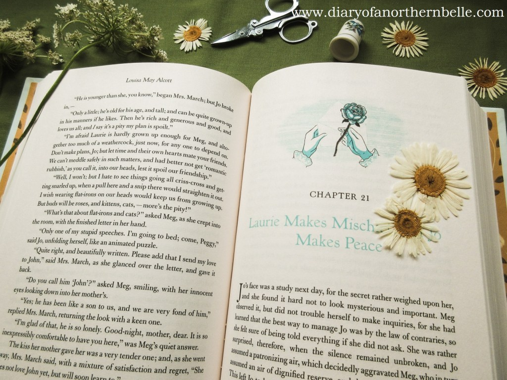 open Little Women book with pressed daisies