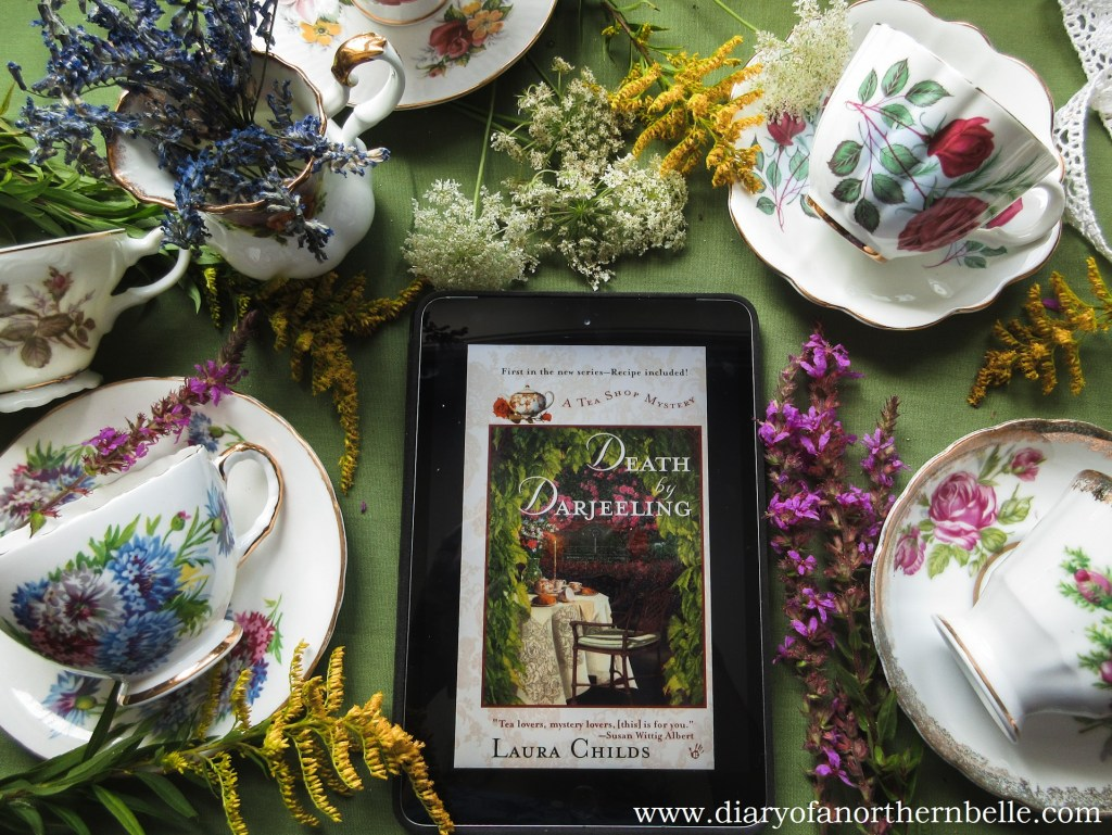 bookcover Death by Darjeeling by inspiring author Laura Childs on iPad surrounded by bone china teacups and wildflowers
