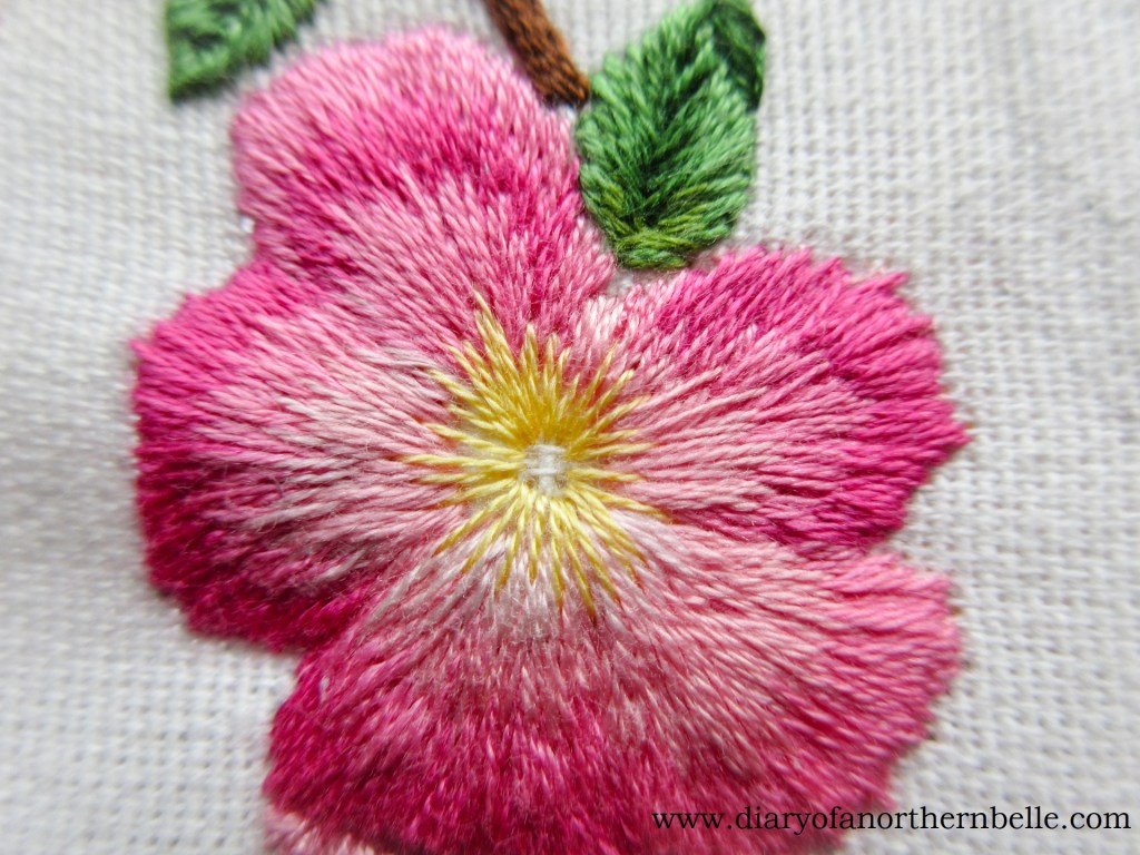 yellow straight stitches to form wild rose center