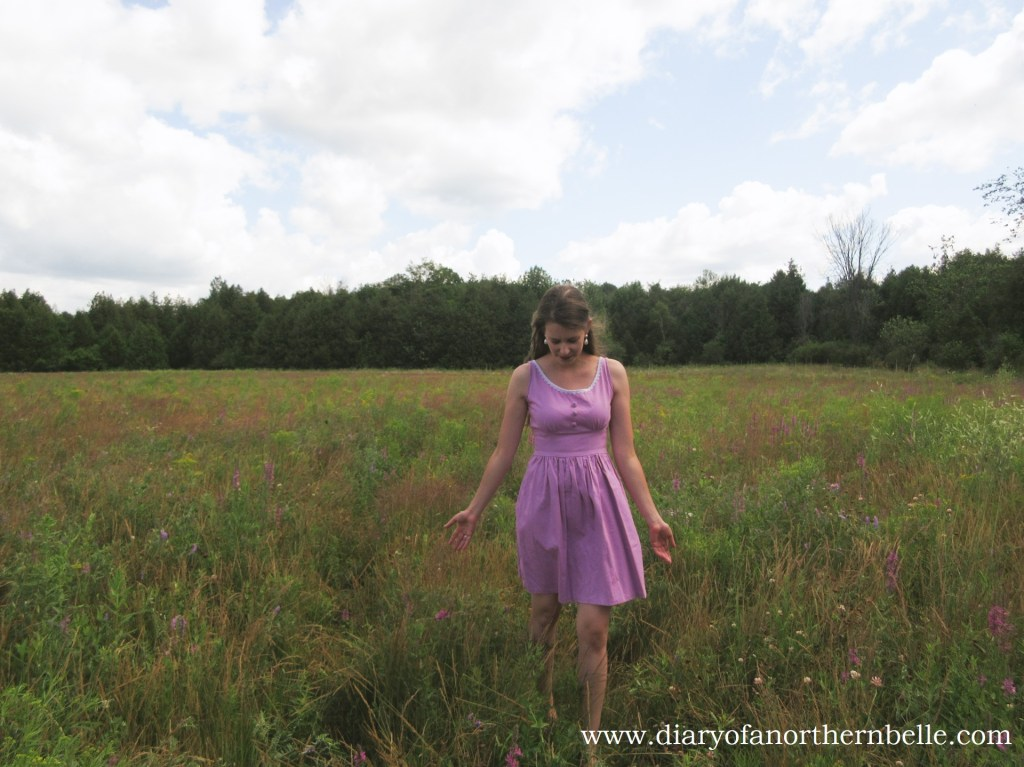 girl in a field wearing lilac dress with embroidered buttons