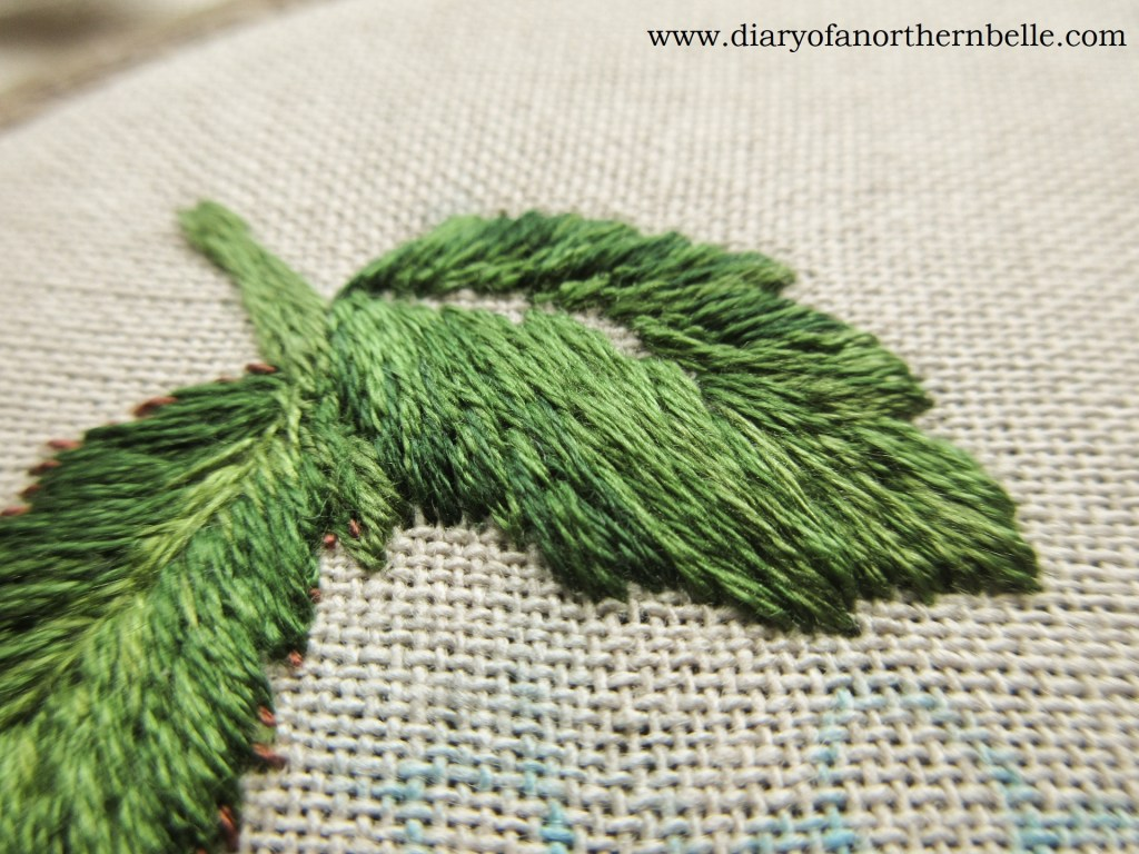 close up of embroidered leaves in long & short stitch
