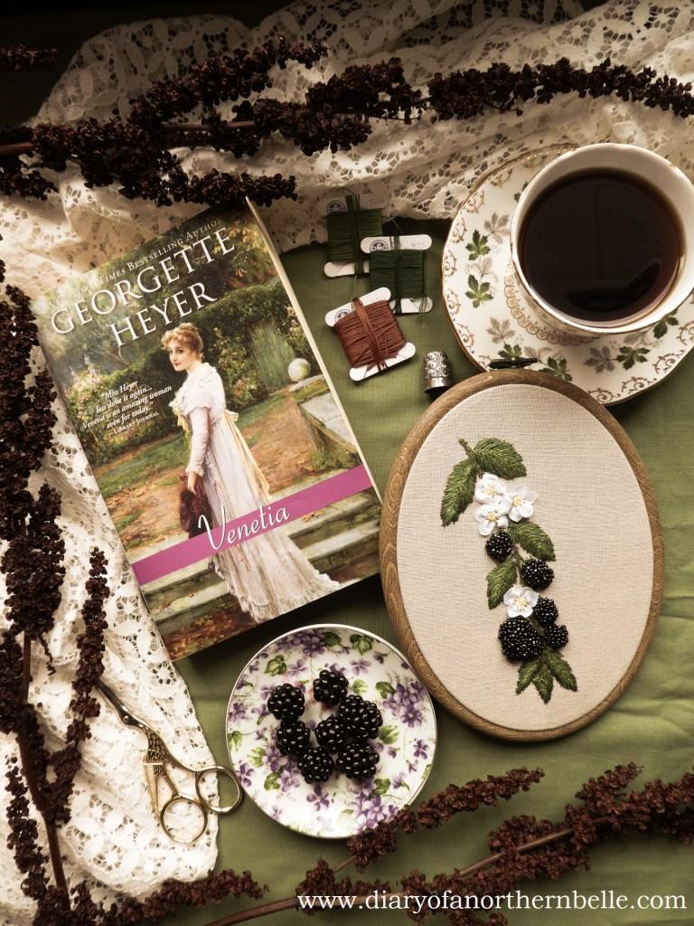 flat lay showing venetia book, beaded blackberries project, plate of blackberries, cup of tea, and dried botanicals