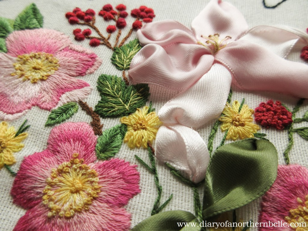 close up of finished embroidery showing more wild roses, currant branch, and lily