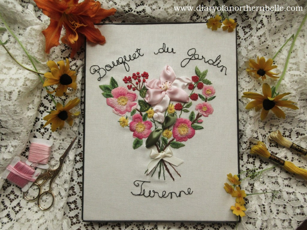 flat lay view of the finished garden bouquet embroidery framed and surrounded by fresh flowers