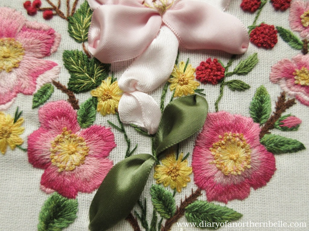 close up of the finished garden bouquet embroidery showing wild roses and lily bud in particular
