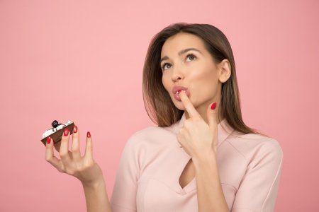 woman licking frosting off finger